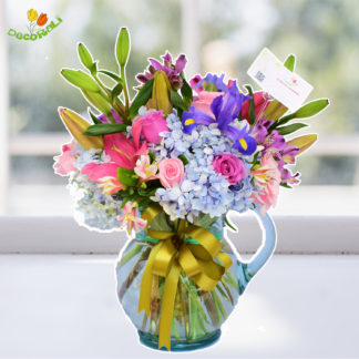Iris rosas y lilis en jarra de vidrio